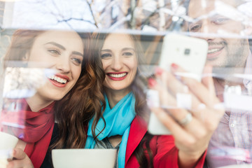 Fashionable young woman showing to her best friends pictures or videos on the mobile phone while sitting together in a trendy coffee shop downtown
