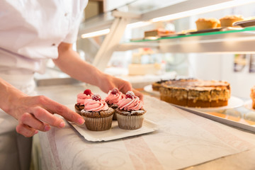 Women putting muffins on display in bakery shop, close-up