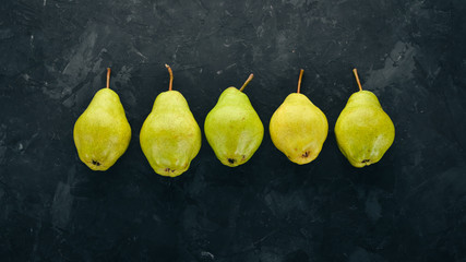 Wall Mural - Fresh pears on a black stone table. Fruits. Free space for text. Top view.