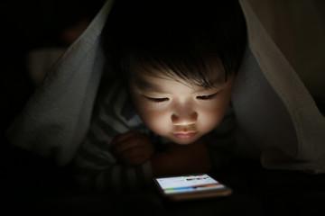 暗い中でスマートフォンを使う男の子