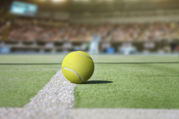 Tennis court background with audience out of focus and close up from a tennis ball