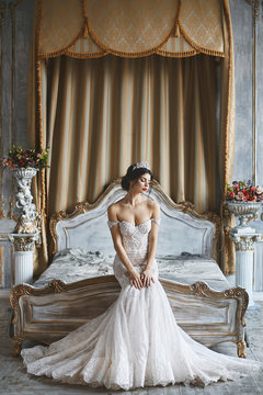 Beautiful young bride, sexy brunette model girl in the stylish and fashionable wedding dress with naked shoulders sits on the bed and posing in luxury vintage interior