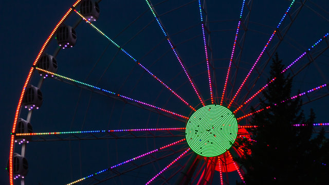Colourful ferris wheel on a dark blue background and with a tree in the front of
