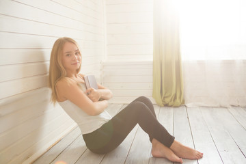 Lovely woman is sitting on the wooden floor with book over window