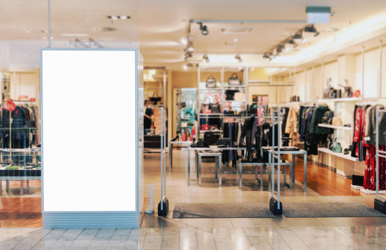 Clothes shop entrance with empty billboard mockup to place text, logo or advertisement