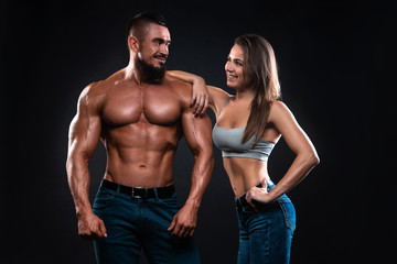 Fitness couple on a black background looking each other and smiling