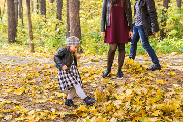 Autumn, seasons and children concept - happy little girl laughing and playing with fallen leaves in park