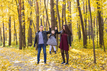 people, family and leisure concept - family with a young daughter walking in autumn park
