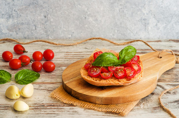 Fresh tomato bruschetta with basil and garlic on rustic background.