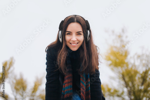 Beautiful girl listening to music on headphones on a nature