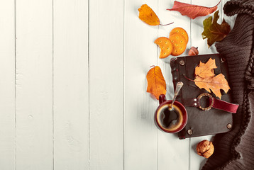 Cup coffee with book in leather binding autumn dry leaf and warm