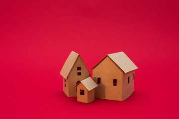 paper houses, red background with copy space, for advertising, side view, close up