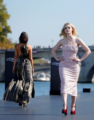 Actor Elle Fanning presents a creation on a giant catwalk installed on a barge on the Seine River during a public event organized by French cosmetics group L'Oreal as part of Paris Fashion Week