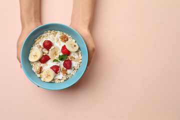 Woman holding bowl with oatmeal and fresh fruits on color background Wall mural