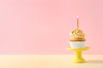 Dessert stand with delicious birthday cupcake on color background