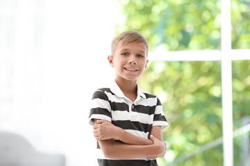 Adorable little boy in casual clothes on blurred background