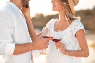 Young couple with glasses of wine on beach, focus on hands