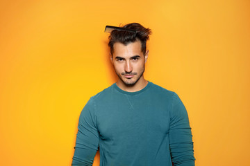Young man with comb posing on color background. Trendy hairstyle