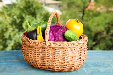 Wicker basket with fresh ripe vegetables on table. Organic food