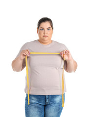 Overweight woman with measuring tape on white background