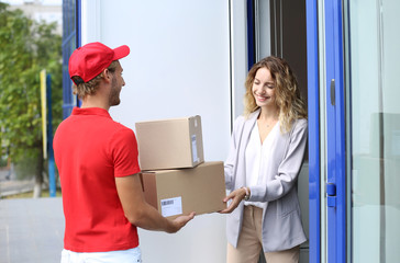 Young woman receiving parcels from courier on doorstep
