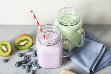 Mason jars with delicious milk shakes and ingredients on table