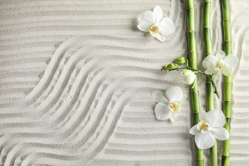 Bamboo branches with flowers on sand, top view. Space for text