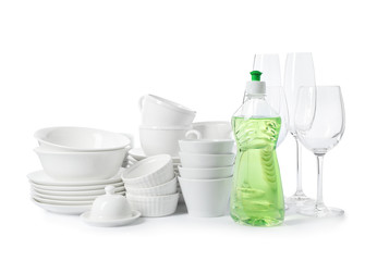 Clean tableware and bottle of detergent on white background. Washing dishes