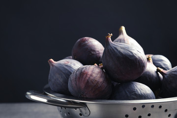 Colander with fresh ripe figs against black background, closeup