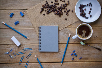 cup of coffee and blank paper on wooden table