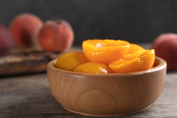 Bowl with conserved peach halves on wooden table. Space for text