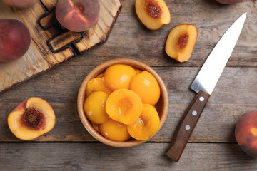 Flat lay composition with canned and fresh peaches on wooden background