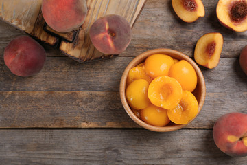 Flat lay composition with canned and fresh peaches on wooden background. Space for text