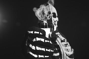man in a terrible mask and black cloak vape