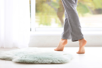 Woman walking barefoot in apartment, closeup. Floor heating