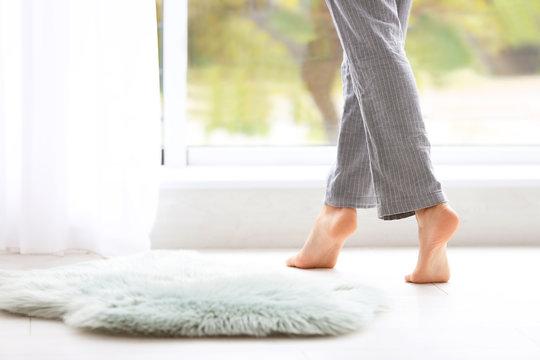 Woman walking barefoot in apartment, closeup. Floor heating