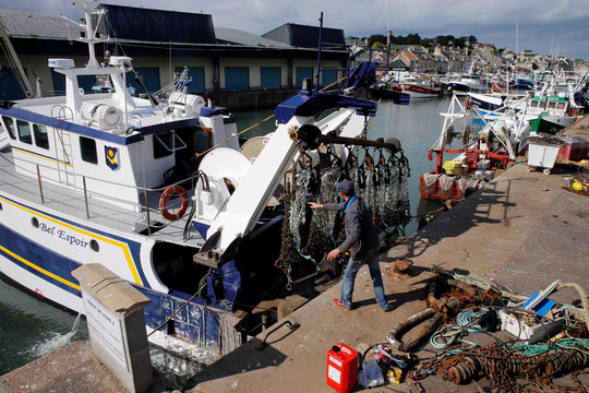 A French fisherman prepares drag nets on the French trawler Bel Espoir before it leaves the harbour of Port en Bessin on the eve of the start of the scallop fishing season