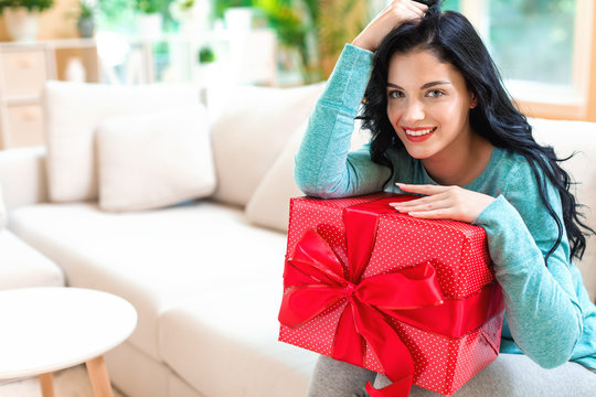 Young woman with a gift box in a bright interior room