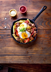 CHILEAN FOOD. CHORRILLANA - french fries topped with beef sliced, tipical sausages chorrisos, fried onion and eggs served in cast iron pan with sauces. Wooden background. top view