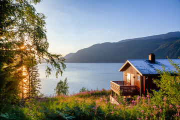Wooden summerhouse with terrace overlooking scenic lake at sunset in Norway Scandinavia