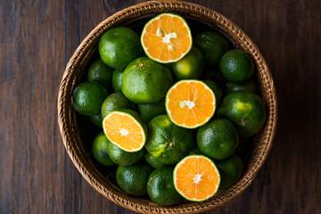 Half Cut Green Tangerine Mandarins in Wooden Bowl.