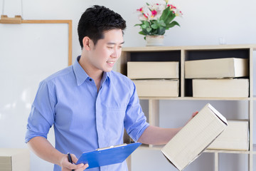 Happy own businessman checking order and packing for shopping online at home office packaging on background is a popular business. Freelance working,online shopping concept