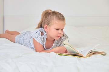 Girl reading lying on bed