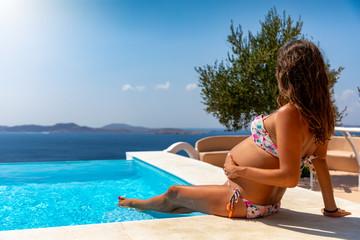 Schwangere Frau im Bikini sitzt am Pool und genießt ihren Schwangerschaftsurlaub in der Sonne