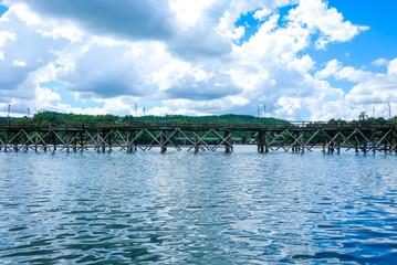 Uttanunan Bridge The bridge is the longest wooden bridge in Thailand,Top Travel Thailand,A wooden bridge crosses the river.