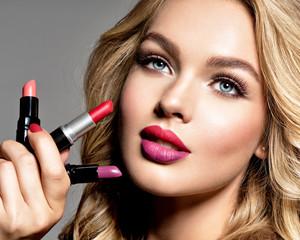 BBeautiful woman holds  lipsticks. Makeup.  Beauty concept