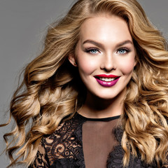 Blond smiling woman with long curly beautiful hair.