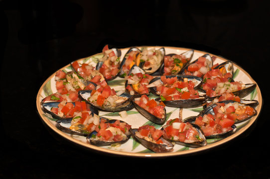 Top view, medium distance, freshly steamed mussels of half shell mixed with olive oil, chopped onion and tomatoes, shredded garlic salt and pepper arranged in circular row on an artisan painted plate
