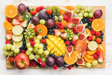Healthy raw fruits and berries platter background, strawberries raspberries oranges plums apples kiwis grapes blueberries, mango on the serving board, top view, selective focus