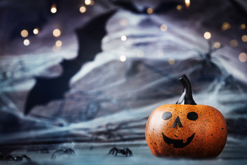 Halloween card with funny pumpkin head, spider, web and flying bat on mystical background.